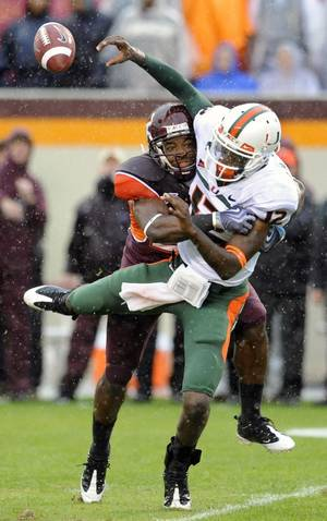 Photo - Virginia Tech defender Josh Porch, left, sacks Miami quarterback Jacory Harris during action last Saturday at Lane Stadium in Blacksburg, Va. AP photo