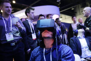 Photo -   Show attendees play a video game wearing Oculus Rift virtual reality headsets Jan. 7 at the Intel booth at the International Consumer Electronics Show, in Las Vegas.  AP File Photo  <strong>Jae C. Hong -  AP </strong>