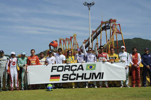 "Photo - In this photo released by Desafio Internacional das Estrelas, pilots taking part in the karting race International Challenge of the Stars hold a banner that reads in Portuguese ""Strength Schumi,"" a message for Michael Schumacher, in Penha, Brazil, Saturday, Jan. 11, 2014. Schumacher, who won the annual karting event in 2007 and 2009, has been in a medically induced coma since Dec. 29, 2013 when he struck his head on a rock while skiing on a family vacation. (AP Photo/Duda Bairros, Desafio Internacional das Estrelas)"