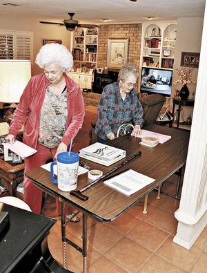 Photo - Ann Tubbs, left, a precinct inspector for the Comanche County Election Board, and Doris Recer-Ensley, precinct judge, set up for school board elections Tuesday in Tubbs' living room in Lawton. Photo by  Jeff Dixon, Lawton Constitution