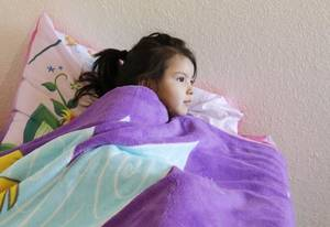 Photo - Ryleigh Genn, 4, curls up under the blanket of her new bed during a delivery for Hope Chest Ministries in Oklahoma City, Saturday, February 22, 2014. Photo by Doug Hoke, The Oklahoman