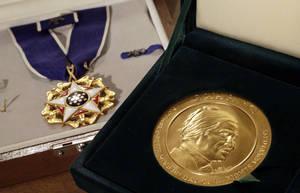 Photo - In this  March 14, 2014 photo, Rosa Parks' Presidential Medal of Freedom, left, and her  Congressional Gold Medal are displayed at Guernsey's  auction house, in New York. A years-long legal fight between Parks' heirs and her friends led to memorabilia being taken away from her home city of Detroit and offered up to the highest bidder. But so far, no high bidder has emerged. (AP Photo/Richard Drew)