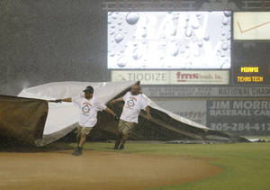 Photo - Grounds crew workers put a tarp over the field during a rain delay in the sixth inning of  an NCAA college baseball regional tournament between Miami and Texas Tech in Coral Gables, Fla., Sunday, June 1, 2014.  (AP Photo/Lynne Sladky)