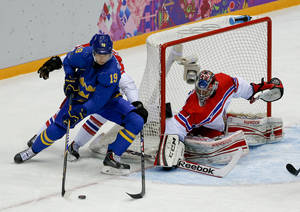 Photo - Sweden forward Nicklas Backstrom tries to wrap the puck around the goal against Czech Republic goaltender Jakub Kovar in the first period of a men's ice hockey game at the 2014 Winter Olympics, Wednesday, Feb. 12, 2014, in Sochi, Russia. (AP Photo/Julio Cortez)