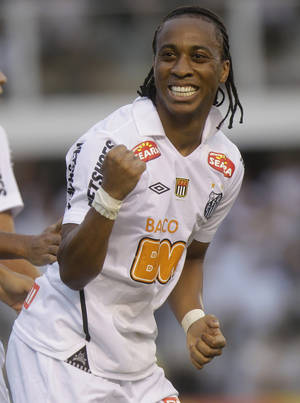 "Photo - FILE - In this May 15, 2011 file photo, Santos' Arouca celebrates after scoring against Corinthians, during their Sao Paulo league soccer final match, in Santos, Brazil.  Arouca, who played for Brazil's national team last year, was on the field talking to reporters after his team's 5-2 win in the Sao Paulo state championship on Thursday when some fans in the stands called him ""monkey."" (AP Photo/Andre Penner, File)"