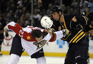 photo - Florida Panthers defenseman Tyson Strachan (23) loses his helmet during a fight with Buffalo Sabres center Cody McCormick (8) during the first period of an NHL hockey game in Buffalo, N.Y., Sunday, Feb. 3, 2013. (AP Photo/Gary Wiepert)
