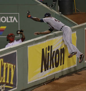 Photo - Detroit Tigers' Torii Hunter leaps and misses a catch as Boston Red Sox's David Ortiz hits a grand slam home run in the eighth inning during Game 2 of the American League baseball championship series Sunday, Oct. 13, 2013, in Boston. (AP Photo/Charlie Riedel)
