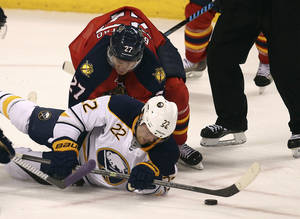 Photo - Florida Panthers' Nick Bjudstad (27) and Buffalo Sabres' Johan Larsson (22) battle for the puck during the second period of an NHL hockey game in Sunrise, Fla., Friday, Oct. 25, 2013. (AP Photo/J Pat Carter)