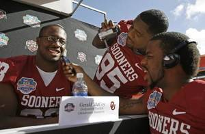 Photo - Oklahoma's Gerald McCoy,left, is interviewed by teammates Alan Davis and Lendy Holmes during media day at Dolphin Stadium today. AP Photo