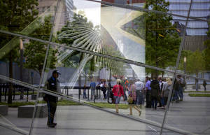 Photo - FILE - With an image of the former World Trade Center seen through the reflective windows of the 9/11 Memorial Museum, some of the first public visitors can be seen arriving at the site in New York in this Wednesday, May 21, 2014 file photo. Organizers say over 300,000 people have visited the Sept. 11 museum since it opened little more than a month ago, and that has exceeded their expectations. (AP Photo/Craig Ruttle, File)