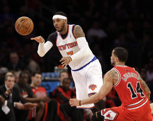 Photo - New York Knicks' Carmelo Anthony, left, passes the ball past Chicago Bulls' D.J. Augustin during the first half of the NBA basketball game, Sunday, April 13, 2014 in New York. The Knicks defeated the Bulls 100-89. (AP Photo/Seth Wenig)