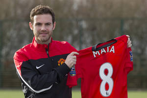 Photo - Manchester United's new signing Juan Mata displays his new shirt before a press conference at the team's Carrington training ground, Manchester, England, Monday, Jan. 27, 2014. With Manchester United in danger of missing out on the Champions League next season, Juan Mata's arrival at Old Trafford for a club record fee of 37.1 million pounds ($61.2 million) is certainly an emergency move. But it also marks the first step in the rebuilding process of England's most titled club. After a botched transfer campaign last summer that was followed by the club's lackluster first half of the season, United now looks determined to allow manager David Moyes the opportunity to build his own team.(AP Photo/Jon Super)