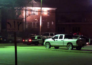 photo - Law enforcement vehicles surround the backside of an apartment complex evacuated by authorities as they hunt for a 22-year-old man suspected of fatally shooting two police officers, Sunday, Dec. 16, 2012, in Topeka, Kan. Two Kansas police officers were shot outside the store on Sunday while responding to a report of a suspicious vehicle and died later at a hospital, authorities said. (AP Photo/The Topeka Capital Journal, John Hanna)