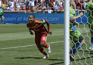 """Photo - Real Salt Lake forward Joao Plata rushes to congratulate Luke Mulholland after Mulholland's shot gave the team a 2-0 lead early in the second half against the Seattle Sounders in an MLS soccer game Saturday, Aug. 16, 2014. The goal was listed as an """"own goal"""" on Seattle's Osvaldo Alonso. (AP Photo/The Salt Lake Tribune, Scott Sommerdorf)"""