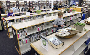 Photo - Library aides shelve reserved books as a part of the new system at the Edmond branch of the Metropolitan Library System.
