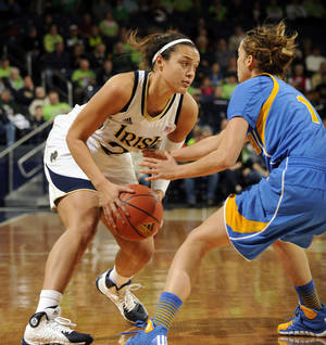 Photo - Notre Dame guard Kayla McBride, left, drives the lane as UCLA guard Thea Lemberger defends during the first half of an NCAA college basketball game, Saturday, Dec. 7, 2013, in South Bend, Ind. (AP Photo/Joe Raymond)