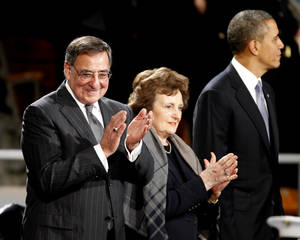 Photo - Outgoing Defense Secretary Leon Panetta, left, and his wife Sylvia, center, applaud as they stand with President Barack Obama during Armed Forces Farewell Ceremony to honor Panetta, Friday, Feb. 8, 2013, at Joint Base Myer-Henderson Hall in Arlington, Va. (AP Photo/Ann Heisenfelt)