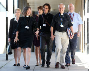 Photo - The Archbishop of Canterbury, Justin Welby, second right, and unidentified members of the clergy, arrive for the General Synod meeting, at The University of York, in York England, Monday July 14, 2014. The Church of England is set to vote on whether women should be allowed to enter its top ranks as bishops. The Church's national assembly, known as the General Synod, is meeting in York, northern England, where it will debate the issue ahead of a vote Monday. (AP Photo/PA,  Lynne Cameron) UNITED KINGDOM OUT