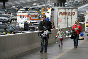 Photo - A family involved a massive pileup accident on Interstate 25, who declined to give their names, walk up the on ramp that leads from South Washington Street onto Interstate 25, in Denver, Saturday, March 1, 2014.  Authorities say one person was killed and 30 others were injured in the giant pileup. (AP Photo/The Denver Post, Kathryn Scott Osler) MAGS OUT; TV OUT; INTERNET OUT; NO SALES; NEW YORK POST OUT; NEW YORK DAILY NEWS OUT