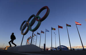 Photo - A man poses for a photo beneath the Olympic rings at Olympic Park, prior to the 2014 Winter Olympics, Monday, Feb. 3, 2014, in Sochi, Russia. (AP Photo/Robert F. Bukaty)