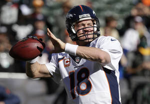 Photo - Denver Broncos quarterback Peyton Manning (18) warms up before an NFL football game against the Oakland Raiders in Oakland, Calif., Sunday, Dec. 29, 2013. (AP Photo/Tony Avelar)