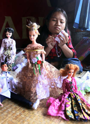 Photo -   In this April 22, 2012 photo, Putu Restiti stitches Barbie dolls dress at her house in Songan village, Kintamani, Bali, Indonesia. Restiti and her sister Alit Astini were kept out of school and had no friends. But like children everywhere, they had powerful imaginations. After being given a Barbie doll, they started stitching tiny, intricate outfits for her from their mother's sewing scraps. And in doing so, they created a new world for themselves. (AP Photo/Firdia Lisnawati)