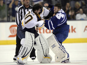 Photo - Buffalo Sabres goalie Ryan Miller fights with Toronto Maple Leafs goalie Jonathan Bernier during the third period of an NHL hockey preseason game in Toronto, Sunday Sept. 22, 2013. (AP Photo/The Canadian Press, Frank Gunn)