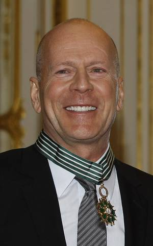 Photo - American movie star Bruce Willis smiles after being awarded with the medal of Commander of Arts and Letters by French culture minister Aurelie Filippetti, in Paris, Monday Feb. 11, 2013.(AP Photo/Remy de la Mauviniere)