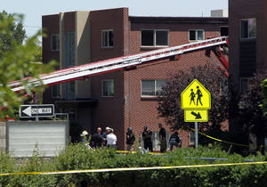 "Photo -   Firefighters and police gather after an explosion could be heard in front the apartment of shooting suspect James Holmes in Aurora, Colo., Saturday, July 21, 2012. Federal authorities detonated one small explosive and disarmed another inside Holmes' apartment, but several other explosive devices remained, said Aurora police Sgt. Cassidee Carlson. Twelve people were killed and dozens were injured in a shooting attack early Friday at a packed movie theater during a showing of the Batman movie, ""The Dark Knight Rises."" Police have identified Holmes, 24, as the suspected shooter. (AP Photo/Ed Andrieski)"
