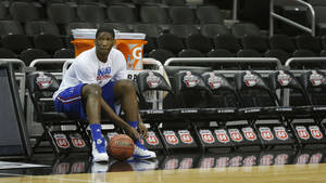 Photo - Kansas center Joel Embiid ties a shoe during practice for their opening NCAA basketball game in the Big 12 men's tournament in Kansas City, Mo., Wednesday, March 12, 2014. Kansas will play the winner of tonight's Texas Tech Oklahoma State game. (AP Photo/Orlin Wagner)