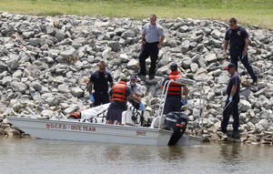 Photo - Oklahoma City Police and Fire Dept. personnel cover a body found partially  submerged on the bank of the Oklahoma River under the Exchange Ave. bridge Monday in Oklahoma City. Photo By Paul Hellstern, The Oklahoman
