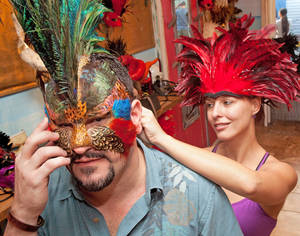 Photo -   In this Oct. 19, 2012, photo provided by the Florida Keys News Bureau, Jessica Marzulla, right, adjusts the fit of a mask on Mark Marien in Key West, Fla., during the first day of Fantasy Fest, the island city's 10-day masking and costuming festival, set to continue through Oct. 28. (AP Photo/Florida Keys News Bureau, Carol Tedesco)