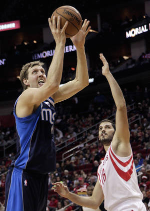 Photo - Dallas Mavericks forward Dirk Nowitzki (41), of Germany, drives past Houston Rockets' Omri Casspi (18) for a layup during the first half of an NBA basketball game, Monday, Dec. 23, 2013, in Houston. (AP Photo/Bob Levey)