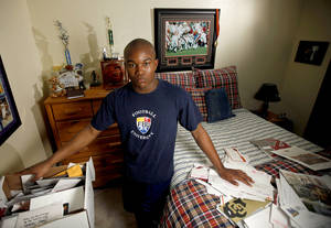 Photo - Heritage Hall's Barry Sanders stands in his room with his recruiting letters.  Photo by Bryan Terry, The Oklahoman