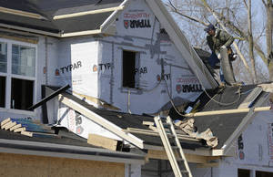 Photo - A builder works on the the roof of a new home under construction on Friday, Dec. 27, 2013., in Wilmette, Ill. (AP Photo/Nam Y. Huh)
