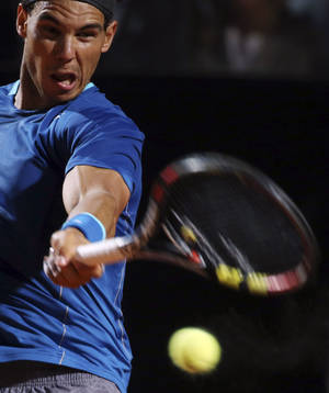 Photo - Spain's Rafael Nadal returns the ball to Bulgaria's Grigor Dimitrov, during their semifinal match at the Italian open tennis tournament in Rome, Saturday, May 17, 2014. Nadal won 6-2, 6-2. (AP Photo/Gregorio Borgia)