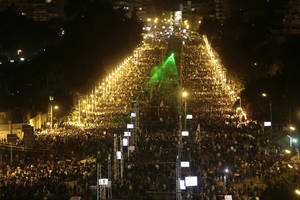 photo - Egyptian protesters gather outside the presidential palace after they broke through a barbed wire barricade that was keeping them from getting closer to the presidential palace, in Cairo, Egypt, Friday, Dec. 7, 2012. Egypt's political crisis spiraled deeper into bitterness and recrimination Friday as thousands of Islamist backers of the president vowed vengeance at a funeral for men killed in bloody clashes earlier this week and large crowds of the president's opponents marched on his palace to increase pressure after he rejected their demands. (AP Photo/Hassan Ammar)