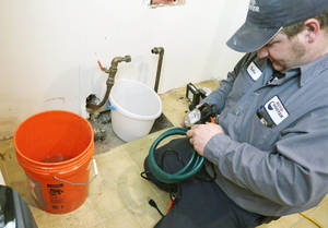 "Photo - Plumber Nate Petersen prepares a pump to shoot water into the incoming city water line, left pipe, that has been frozen Thursday, Jan. 9, 2014, at a south Minneapolis home. Roto Rooter was been ""inundated"" with calls since the cold snap and regular work has been put on hold because of burst pipes and even frozen sewer lines according to plumbing manager Paul Teale. The deep freeze and storms that gripped much of the country over the past week cost the economy as much as $5 billion, by one estimate. (AP Photo/Jim Mone)"