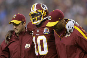 Photo - Washington Redskins quarterback Robert Griffin III is helped off the filed after an injury during the second half of an NFL football game against the Baltimore Ravens in Landover, Md., Sunday, Dec. 9, 2012. (AP Photo/Patrick Semansky)