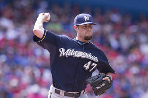 Photo - Milwaukee Brewers pitcher Rob Wooten throws to first base during the eighth inning of a baseball game, Tuesday, July 1, 2014 in Toronto. (AP Photo/The Canadian Press, Chris Young)
