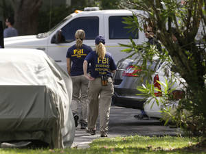 Photo - FBI investigators walk near the crime scene of an apartment where a man was shot by an FBI agent, Wednesday, May 22, 2013, in Orlando, Fla.  The man who was shot and killed by the agent early this morning was friends with the Boston bombings suspects, according to a friend of the victim. (AP Photo/John Raoux)