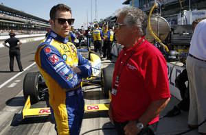 Photo - Marco Andretti, left, talks with his grandfather and 1969 Indy 500 champion Mario Andretti before the start of the final day of practice for the Indianapolis 500 IndyCar auto race at the Indianapolis Motor Speedway in Indianapolis, Friday, May 23, 2014. The 98th running of the Indianapolis 500 is Sunday. (AP Photo/Tom Strattman)