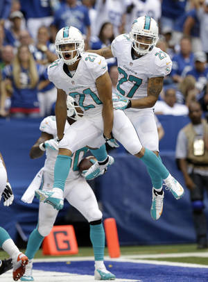 Photo - Miami Diolphins' Brent Grimes (21) celebrates with Jimmy Wilson (27) after Grimes intercepted a pass in the end zone intended for Indianapolis Colts' Reggie Wayne during the second half an NFL football game Sunday, Sept. 15, 2013, in Indianapolis. (AP Photo/Michael Conroy)