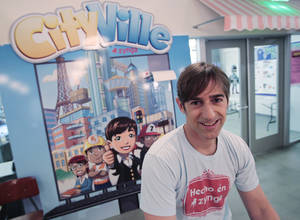 "Photo - In this May 2, 2012 photo, Zynga CEO Mark Pincus smiles in front of one of their popular games ""Zynga CityVille"" at Zynga headquarters in San Francisco. Pincus is stepping down as chief product officer, less than a year after he was replaced as the company's CEO, as the company's sales slide. Zynga said Wednesday, April 23, 2014, that Pincus will remain chairman of the company he founded in 2007. (AP Photo/Paul Sakuma)"