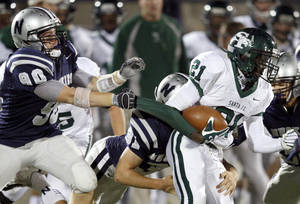photo - Edmond Santa Fe's Ryan Frazier tries to get past Edmond North's Nick Washburn, left, and Ragan Land during a high school football game at Wantland Stadium in Edmond, Okla., Friday, Oct. 29, 2010.  Photo by Bryan Terry, The Oklahoman