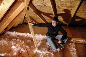 Photo -  Amy Melton points to issues she says exist with the rafters and structure of the roof in the attic of her house in Ada. Photo by Jim Beckel, The Oklahoman  <strong>Jim Beckel -   </strong>