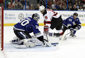 Photo - Tampa Bay Lightning center Steven Stamkos (91) comes in to help goalie Ben Bishop (30) defend on a shot by New Jersey Devils right wing Dainius Zubrus (8), of Lithuania, during the first period of an NHL hockey game Saturday, March 15, 2014, in Tampa, Fla. (AP Photo/Brian Blanco)