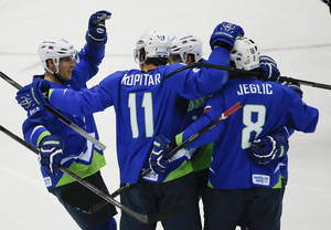 Photo - Slovenia forward Anze Kopitar (11) celebrates with teammates after scoring a goal against Austria in the first period of a men's ice hockey game at the 2014 Winter Olympics, Tuesday, Feb. 18, 2014, in Sochi, Russia. (AP Photo/Julio Cortez)