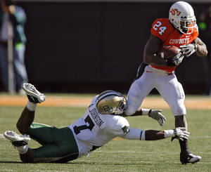 Photo - Oklahoma State's Kendall Hunter (24) runs past Baylor's Antonio Johnson (7) during the college football game between the Oklahoma State University Cowboys (OSU) and the Baylor University Bears at Boone Pickens Stadium in Stillwater, Okla., Saturday, Nov. 6, 2010. Photo by Chris Landsberger, The Oklahoman