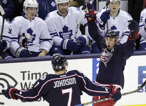 Photo - Columbus Blue Jackets' Brandon Dubinsky, right, celebrates his short-handed goal against the Toronto Maple Leafs with teammate Jack Johnson during the third period of an NHL hockey game on Friday, Oct. 25, 2013, in Columbus, Ohio. The Blue Jackets defeated the Maple Leafs 5-2. (AP Photo/Jay LaPrete)